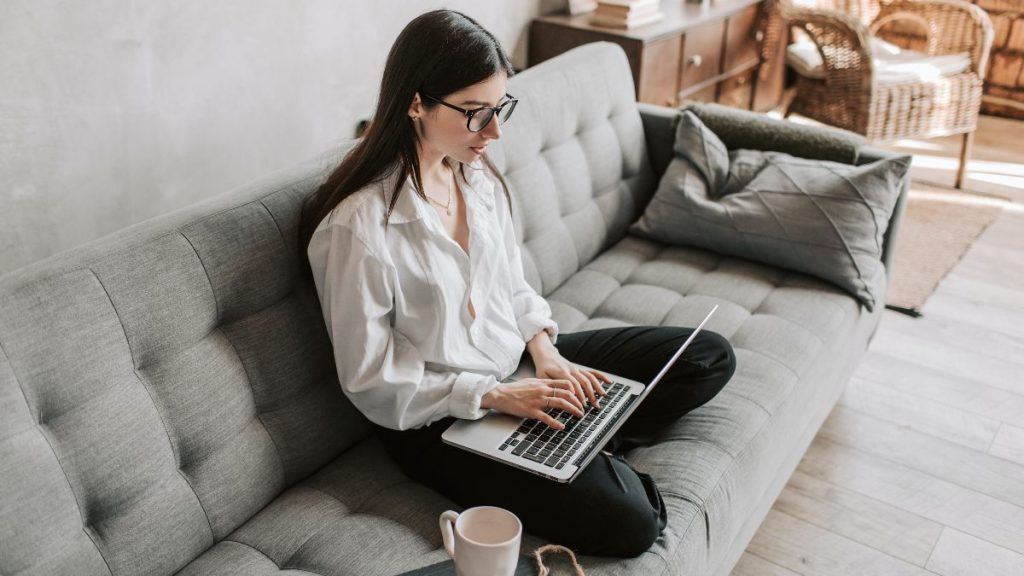 woman sitting on sofa with laptop