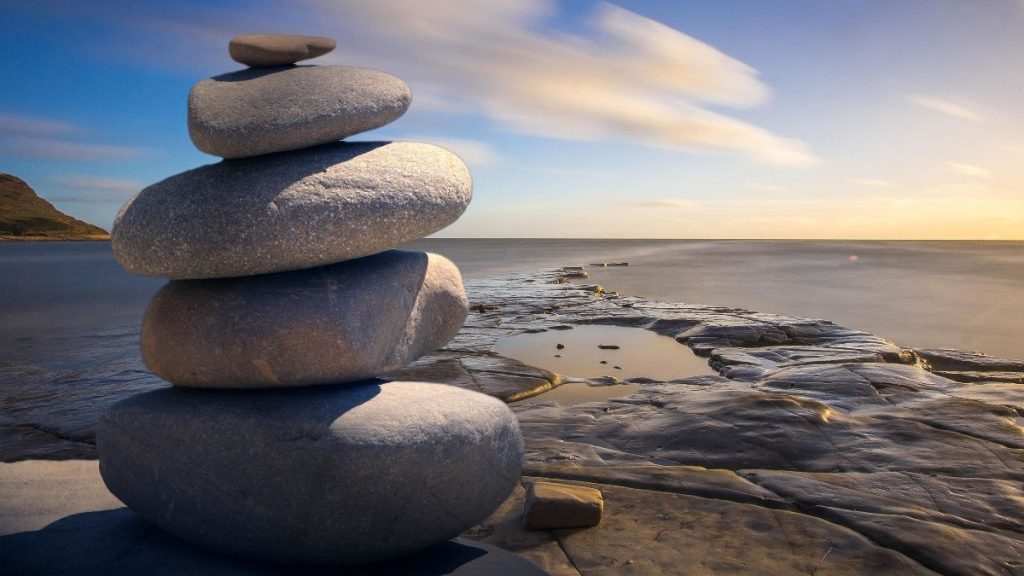 rocks stacked by water - inukshuk