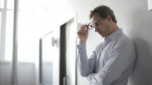 man leaning against wall taking off his glasses