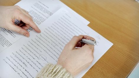 person proofreading paper with pen