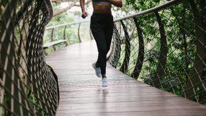 woman running along bridge trail