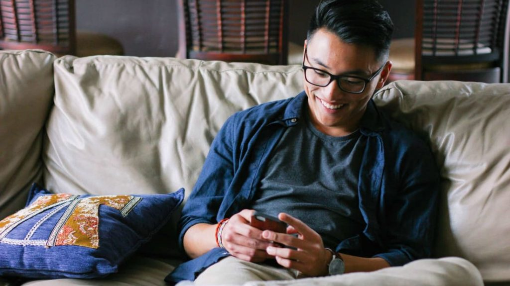 man sitting on sofa looking at phone