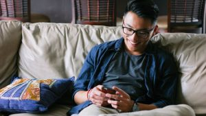 man sitting on sofa looking at phone