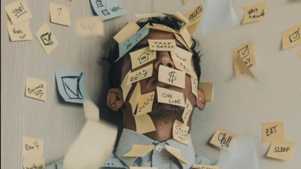 sticky notes on man's face and wall