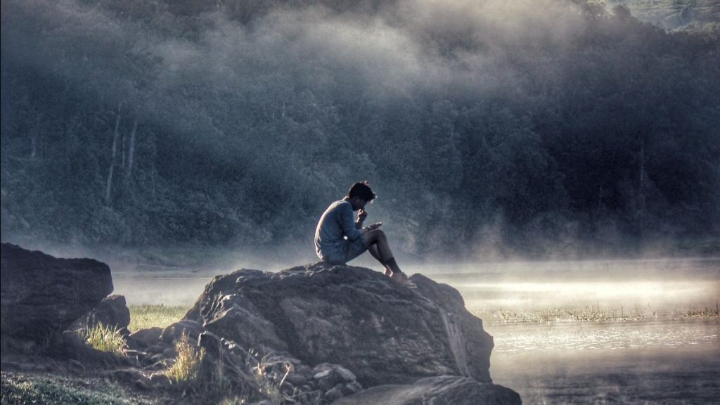 photo of man sitting on rocks by water in the forest