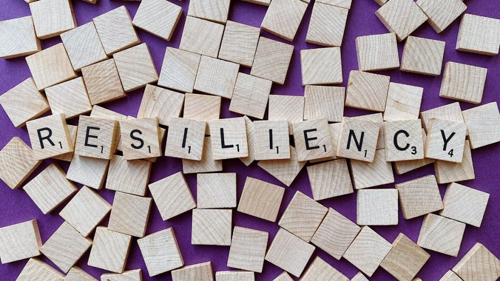 wood scrabble letters spelling resiliency